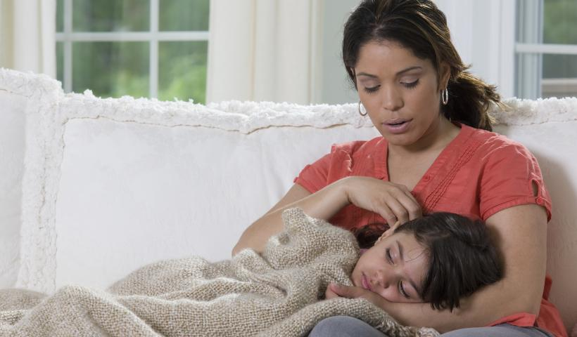An image of a Mother caring for her sick child.
