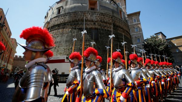 New recruits of the Vatican's elite Swiss Guard march in front of the tower of the Institute for Works of Religion during the swearing-in ceremony at the Vatican