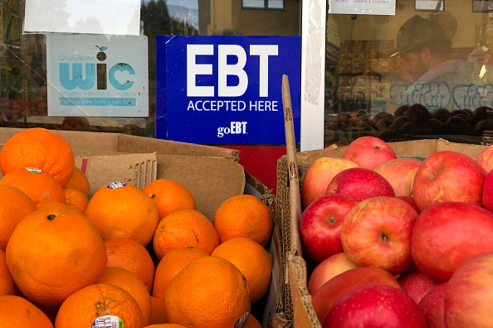 A sign noting the acceptance of electronic benefit transfer (EBT) cards, used to issue benefits from state welfare departments, is displayed at a grocery store on Dec. 4, 2019