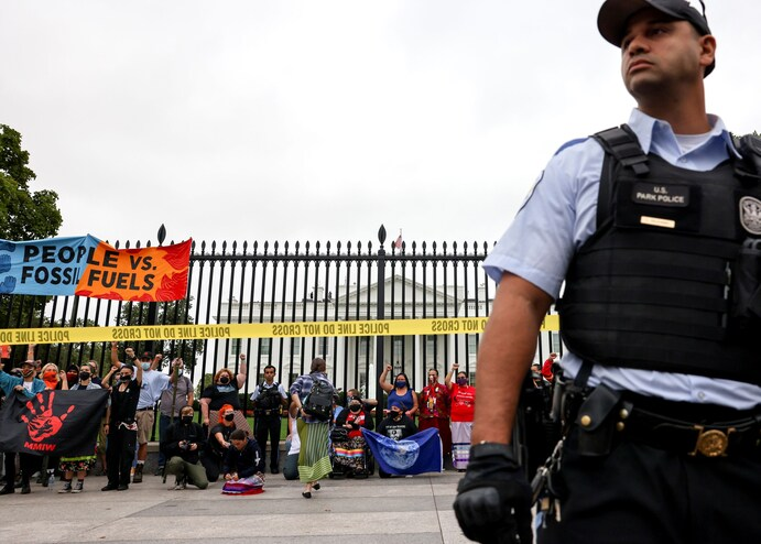 A U.S. Park Police officer looks on as people take part in a climate change protest outside the White House on Oct. 11.